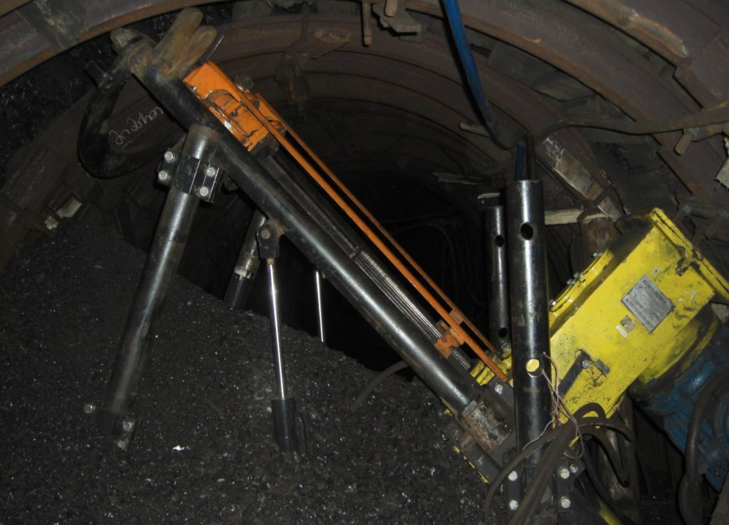 Идет бурение скважины. Уголь вручную отгружается на конвейер, который находится за станком, под электромотором. (Конвейер смонтировали, когда станка еще не было.)